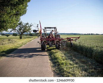 Tractor on a road in summer at the grain harvest with blue sky in Stuttgart. Germany
