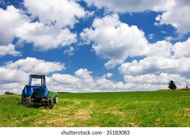 Tractor on the summer field and amazing sky with white clouds