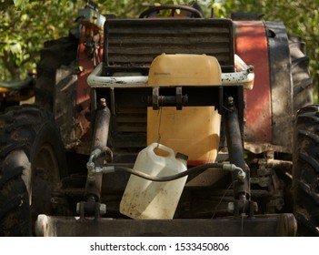 The tractor is parked underneath the walnut trees on there grass, the machine is about to be used to harvest the crops in the walnut orchards of the Dordogne. (Point of focus machine plastics).