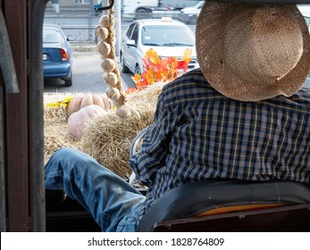 Tractor in the parking lot near the supermarket. Pumpkins on the hay and garlic on a tractor next to a stuffed tractor driver.Horizontal view. Technology to attract the attention of a potential buyer.