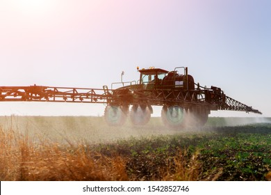 Tractor with pesticide fungicide insecticide sprayer on farm land top view Spraying with pesticides and herbicides crops