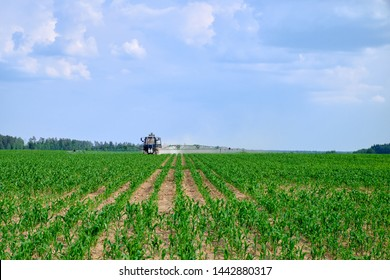 tractor, photographed in the agricultural field during handling pesticides. sky with clouds, against the blue sky with clouds