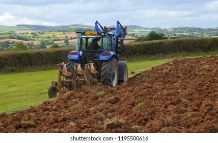Tractor ploughing field in Axe Valley in Devon