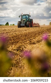 A tractor ploughing a field of crops. Shallow depth of field with selective focus on the tractor.