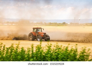 Tractor ploughing the field in sunset with dust in the air