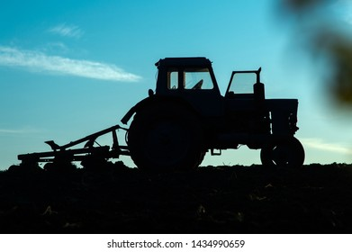 tractor with a plow plowing land on a field in the early morning at sunrise