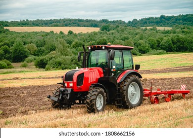 Tractor with plow, Small scale farming with tractor and plow in field. Heavy agricultural machinery for field work