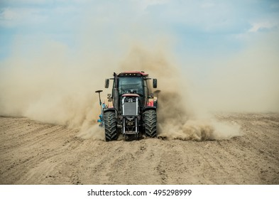 Tractor plowing dry farm land at autumn
