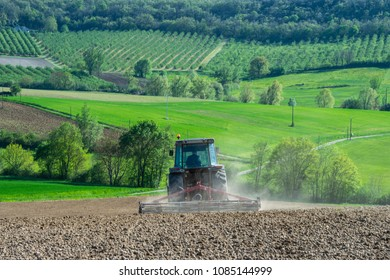 Tractor plowing field and beautiful landscape, France, Europe