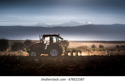 Tractor plowing fields in the andes of Huancayo, Junin, Peru with Hauytapallana mountain at  babackground