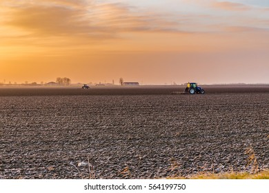 tractor plowing fields in the countryside of Emilia Romagna in Italy at sunrise