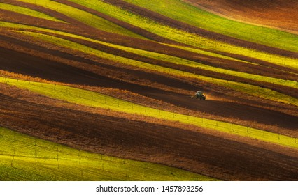 Tractor plowing fields in souther moravia rolling hills. Agriculture symbol minimalist art style landscape background. Farming machinery at work. Czech republic.