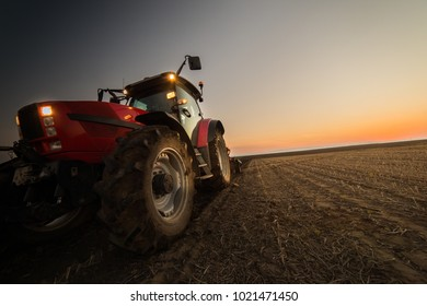 Tractor plowing plow the field on a background sunset.