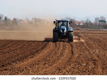 Tractor plows the dry agricultural field  raising dust, in a sunny morning of early springtime