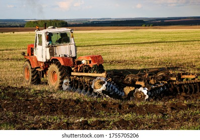 the tractor plows and harrows the land in a large field on a sunny spring day. preparing the soil for planting crops, plowing the soil with a tractor with a disk plow.