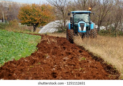 A tractor plows an uncultivated agricultural land for sowing,  in the last days of autumn. Alongside there is a green cultivated field