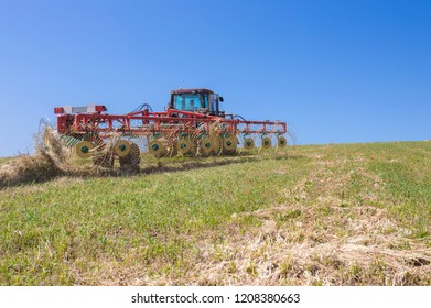 Tractor raking hay over sloped ground. Heavy wire spokes wheels made are pulled by a tractor for gather furrows of cut hay