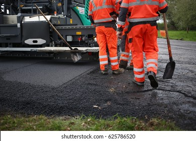 Tractor, roller  on the road repair site. Road construction equipment. Road repair concept. Construction workers on road repair.