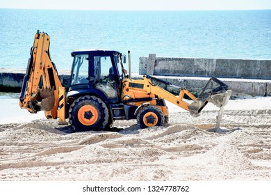 Tractor and sand. Repair work on the beach.