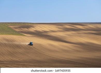 Tractor con taladro de semillas en el paisaje de primavera temprana