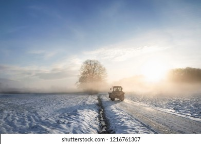 Tractor silhouette on a snowy road, crossing an agricultural field covered in snow, through the mist, at sunrise.