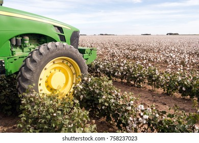 The tractor sits at the cotton plantation farm field edge waiting for harvest