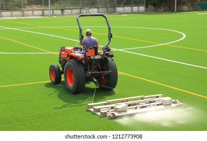 tractor in a soccer stadium putting sand in a new artificial grass