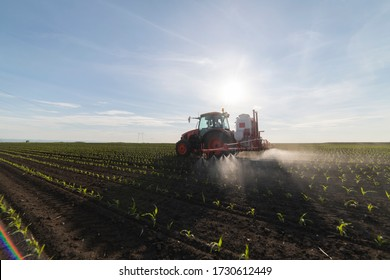 Tractor spray fertilize field with insecticide herbicide chemicals in agriculture field