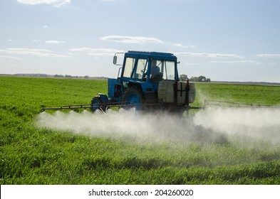 Tractor spray fertilize field with insecticide herbicide chemicals in agriculture field and evening sunlight