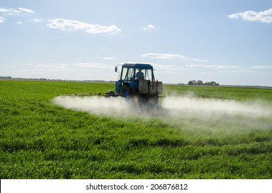 Tractor spray fertilize on green agricultural farm field with pesticide insecticide herbicide chemical in evening sunlight