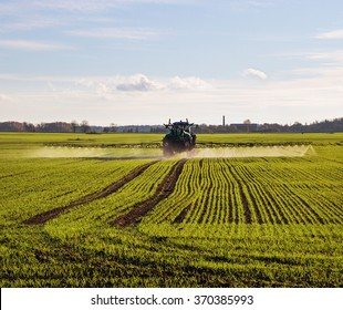 Tractor with sprayer on a wheat field.
