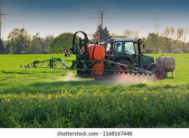 Tractor with sprayer works on a field
