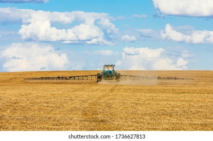 Tractor spraying crops on the prairies