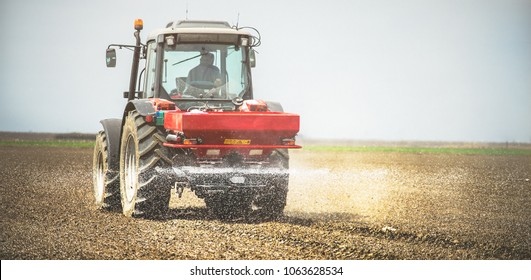 Tractor spraying fertilizer on the soil. Early spring time, Maintaining soil fertility, improving crop development.
