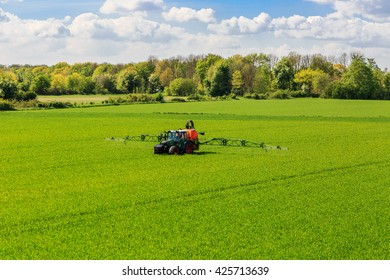tractor spraying glyphosate pesticides on a field