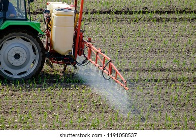 Tractor spraying pesticide on a field with young plants