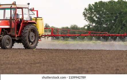 Tractor spraying pesticides on arable fields with sprayer