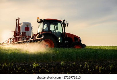Tractor spraying pesticides over a green field