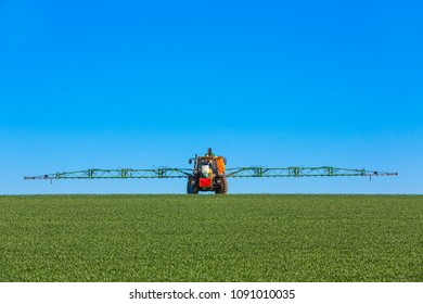 tractor spraying weed killer on the field