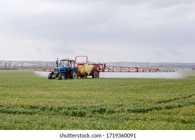 tractor sprays the field with fertilizers