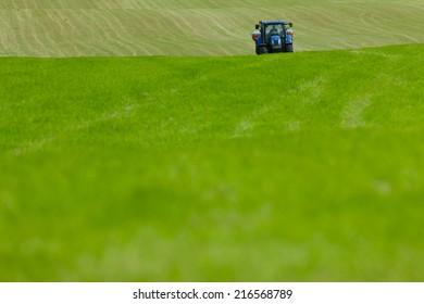 Tractor spreading fertilizer in field