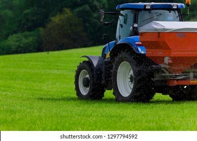 Tractor spreading fertilizer on crops in farm field