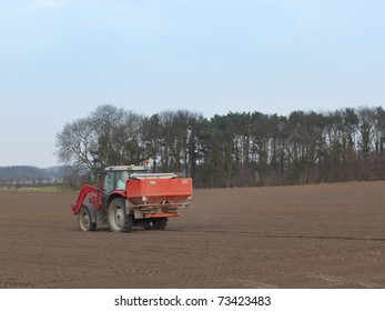 a tractor spreading fertilizer on a cultivated field in springtime under a blue sky