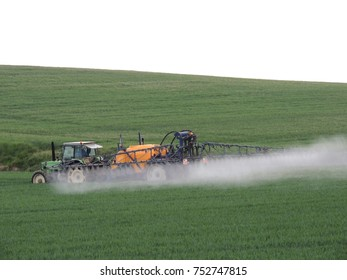 Tractor spreading herbicide on crop.