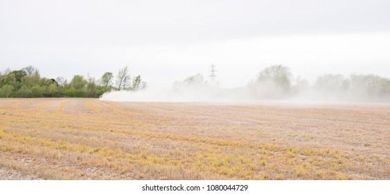 Tractor spreading white powder fertilizer on a field