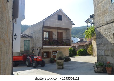 Tractor And Stone Fountain Next To A Stone House In The Beautiful Village Of Combarrro. Nature, Architecture, History, Street Photography. August 19, 2014. Combarro, Pontevedra, Galicia, Spain.