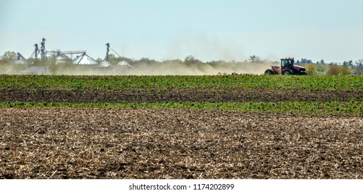 Tractor tilling a field near granary in northern Illinois, USA, for themes of agriculture and spring