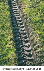 Tractor tire tracks in green grass. mud in spring - vintage retro look