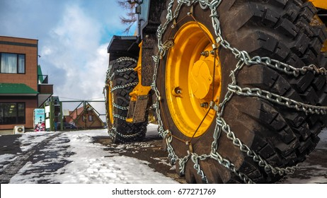 Tractor tires with chains in the snow.