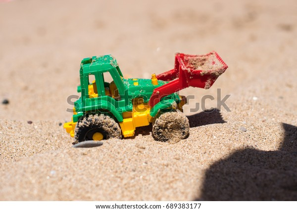 Tractor toy on the sandy beach